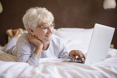 Busy senior woman in bed Royalty Free Stock Photography