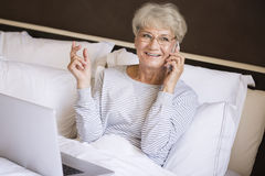 Busy senior woman in bed Stock Photos
