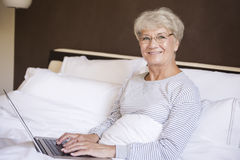 Busy senior woman in bed Stock Photography