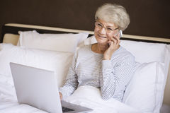 Busy senior woman in bed Stock Image