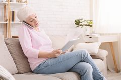 Busy senior woman consulting client on phone and reading contract. On digital tablet at home, empty space royalty free stock images