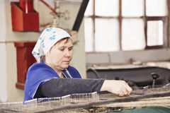 Busy senior worker at machine Stock Photo