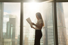 Busy serious businesswoman holding reading document, standing ne Stock Photography