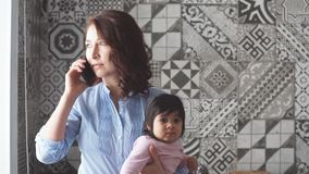 Busy serious mother holding her baby and talking on the smartphone. stock footage