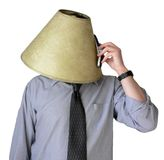 Busy Signal. Businessman with a lampshade on his head, trying to talk on his cell phone stock image