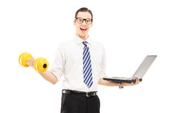 Busy smiling businessman holding a laptop and lifting a dumbbell Royalty Free Stock Images