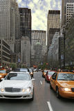 Busy street. In a large city with skyscrapers and cars. Many yellow taxi-cabs Royalty Free Stock Photo