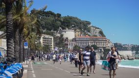 Busy street along waterfront on sunny windy day, people and bikers moving around. Stock footage stock footage