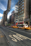Busy street in the center of Manhattan with large buildings and blue sky Stock Photography