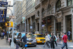 Busy street in Manhattan. New York City, USA - May 19, 2014: A small street with shops in lower manhattan. Cars waiting at traffic lights - pedestrians walking Stock Images