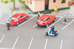 Busy street with miniature people, cars and scooter stock photos
