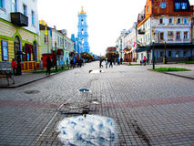 Busy street of a small town of Sumy in Ukraine. The street can be seen old motley houses, Transfiguration Cathedral, the puddles from the rain and the people who Royalty Free Stock Photos