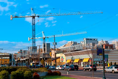 A busy street with two cranes in the background. Two Cranes against a blue sky. Heavy traffic and storefronts in the foreground Stock Photo