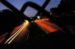 Busy Streets. A busy highway at night shot through a chain link fence stock image