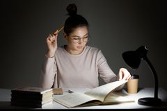Busy student absorbed in reading, wears round transparent glasses for good vision, uses reading lamp, sits at workplace, works in royalty free stock image