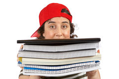 Busy student woman. Busy young student woman with red cap carrying stacked files over a white background. Eyes on focus and shallow DOF Royalty Free Stock Photography