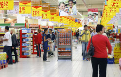Busy supermarket. Customers shopping between the shelves, in the aisle inside a crowded supermarket Stock Images