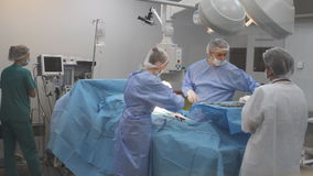 Busy surgery room in hospital. Large medical team performs a complex operation in the surgery room, in a hospital
