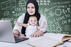 Busy teacher and baby using laptop in class Stock Photo