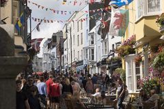 Busy Tenby street. Holiday makers crowd a street of Victorian and Georgian buildings in Tenby, coastal town in Pembrokeshire South Wales. A Welsh flag flies from stock photos