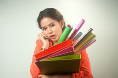 Busy Asian business woman with a lot of folders and colorful papers on background. Stock Images