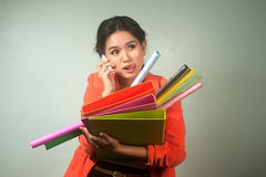 Busy Asian business woman with a lot of folders and colorful pap Stock Images