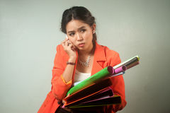 Busy Asian business woman with a lot of folders and colorful pap Royalty Free Stock Photo