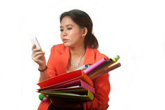 Busy Asian business woman with a lot of folders and colorful papers on isolated background. Stock Photo