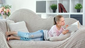 Busy thoughtful young female child reading book lying on couch at cozy living room full shot. Focused casual barefoot teenage girl relaxing enjoying weekend at stock video footage