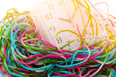 Busy time, clock is wrap with tangled yarn Royalty Free Stock Photo
