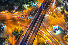 Long exposure of a busy city in a night with cars creating interesting light trails from their headlamps. Light trails of cars and the city lights shows a hectic Stock Images