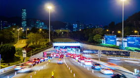 Busy Traffic Going Into Tunnel at Night.  Zoom Out Shot. Hong Kong rush hour sunset timelapse. Commercial Office Buildings with commercial billboards. Busy cars stock video footage