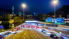 Busy Traffic Going Into Tunnel at Night. Zoom In Shot. Hong Kong rush hour night timelapse. Commercial Office Buildings with commercial billboards. Busy cars stock footage