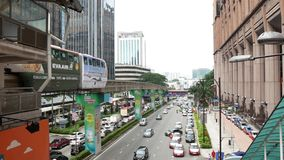 Busy traffic and KL monorail arriving to station Imbi which is directly in front of Times Square Jalan Imbi, Kuala Lumpur Malaysia. Kuala Lumpur, Malaysia stock video