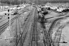 Busy trainyard with many trains on multiple switching tracks in. Black and white Royalty Free Stock Photo