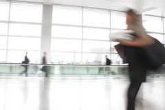 Busy travelers rushing through an airport. Busy travelers rushing through the corridor of an airport, some along a moving walkway royalty free stock images