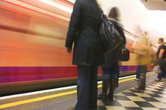 Busy underground station platform train coming by fast Royalty Free Stock Photography