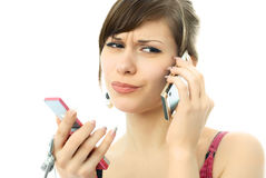 Busy unhappy beautiful woman with two cellphones Royalty Free Stock Photo