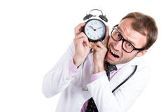 Busy unhappy male doctor holding an alarm running out of time Royalty Free Stock Images