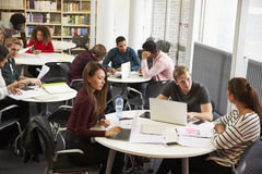 Busy University Library With Students And Tutor Royalty Free Stock Image