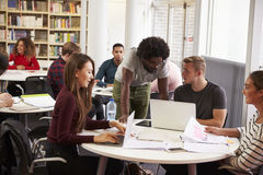 Busy University Library With Students And Tutor Stock Image