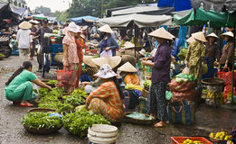 Busy Vietnamese Market Scene. A vegetable market in Hue, Vietnam bustles with early morning vendors and fresh vegetables Stock Photo