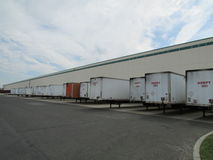 Busy warehouse in NJ, USA. Warehouse bays with trailers being loaded or unloaded in NJ, USA Stock Photography