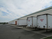 Busy warehouse in NJ, USA. Warehouse bays with trailers being loaded or unloaded in NJ, USA Stock Images
