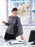 Busy woman arriving at office. Drinking coffee stock photography