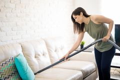 Busy woman cleaning sofa with vacuum cleaner. Pretty young housewife using vacuum machine to clean corners of sofa in living room Royalty Free Stock Photos