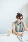 Busy woman designer having lunch in office. Stock Photo