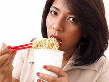 Busy woman eats instant noodles Stock Photo