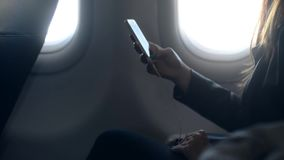 Busy woman holding telephone in hand and sitting in airplane stock footage