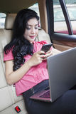 Busy woman with laptop and cellphone in car Stock Image